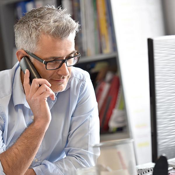 uomo sorridente alla scrivania mentre parla al telefono