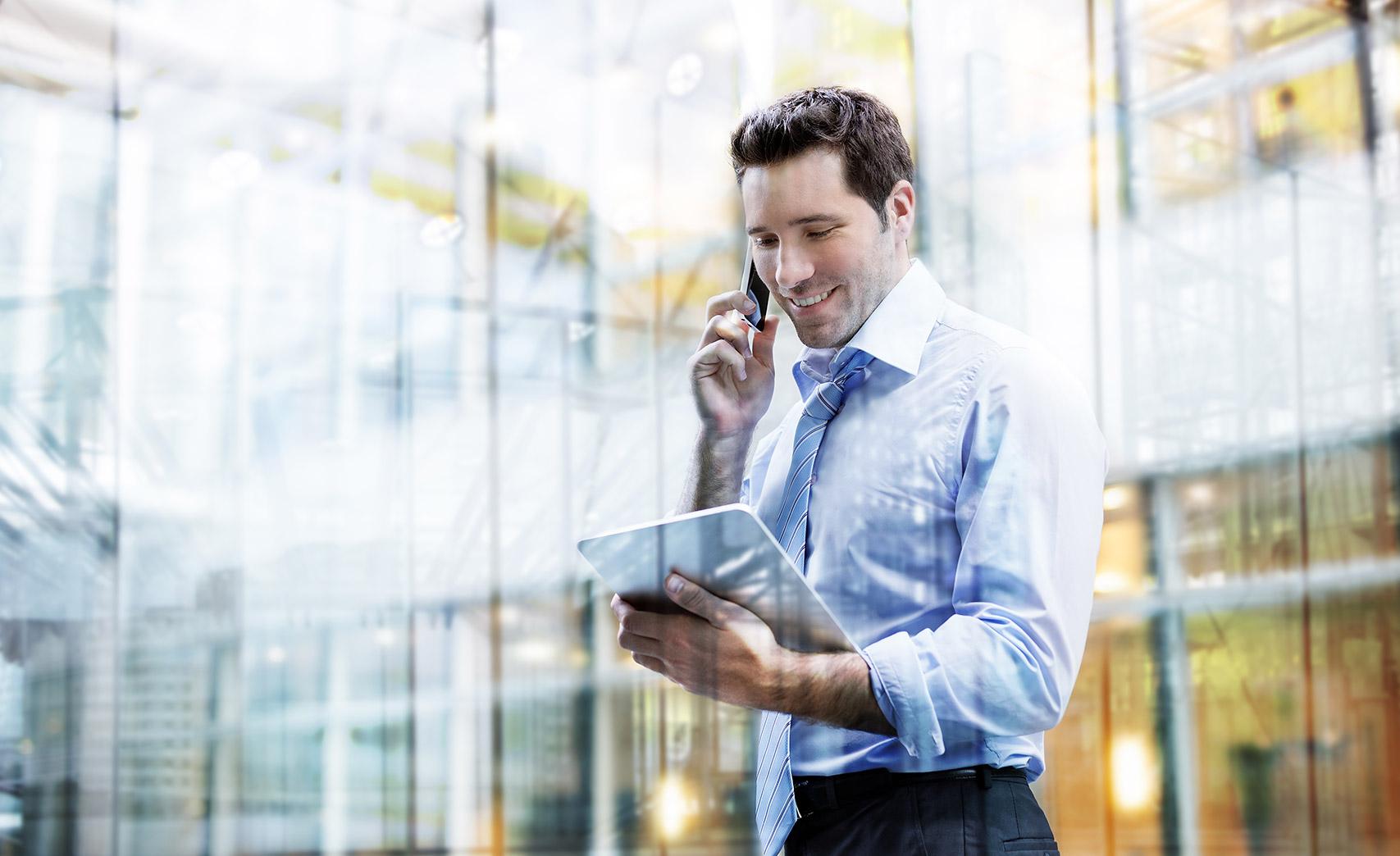 giovane processionista parla al telefono tenendo in mano un tablet.